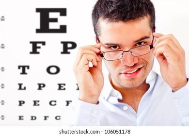Man taking an eye exam and wearing glasses