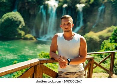 Man taking frend behind waterfall