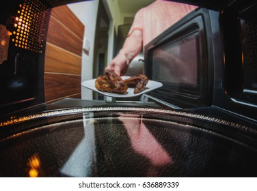 Man taking grilled chicken from microwave oven. inside view