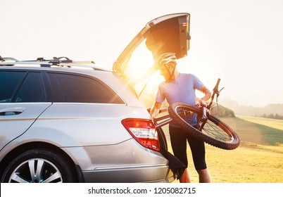 Man taking his bicycle out from the trunk of a car