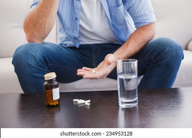 Man taking his pills on couch in the living room
