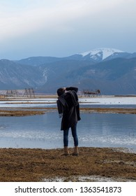 A man is taking landscape photography where has the snow mountain and lake in China.