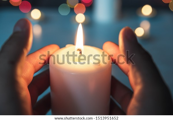 Man taking a lighted candle in his hands. Prayer and meditation at burning candle flames. Symbol of eternity and remembrance of the dead. Religious tradition. Saints' Day. Bokeh background.