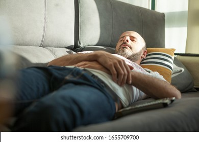 Man taking a nap on the sofa at home while the sunset sun comes through the window illuminating his face