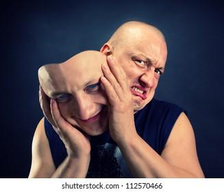 Man taking off his happy facial mask