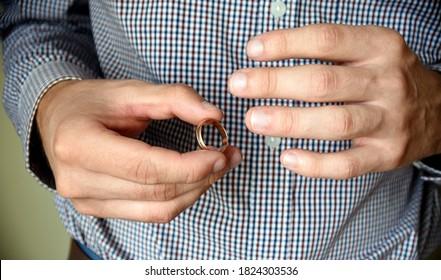 Man taking off his wedding ring. concept of treason, infidelity, betrayal.