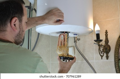 Man taking out an old water heater with scale deposition from a boiler in a bathroom