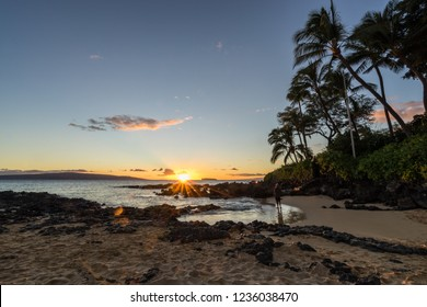 A man taking a photo of the beautiful sunset in Makena Cove, Hawaii