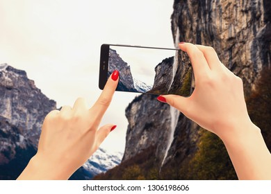 Man taking a photo of the Eiger mountain using the camera Close-up shot of the hand holding the phone with the mountain behind.