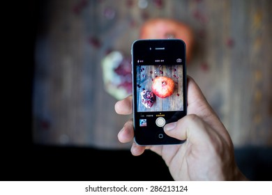 man taking a photo with his smart phone of organic pomegranate open cut in half and full one on a wooden dark table background decorated in rustic style