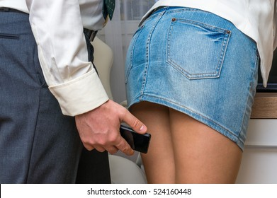 Man taking photo with mobile phone of woman's butt - sexual harassment in business office