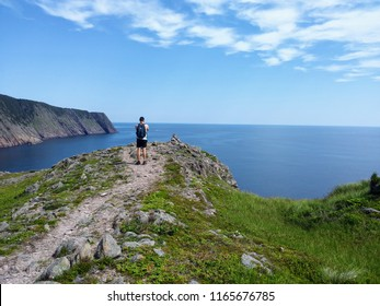 Man taking a photo on his camera of the open and calm atlantic ocean along the sugarloaf trail in Newfoundland and Labrador, Canada