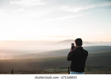 Man taking photo on phone at sunrise