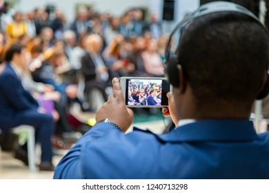 man taking photo on smartphone at a meeting