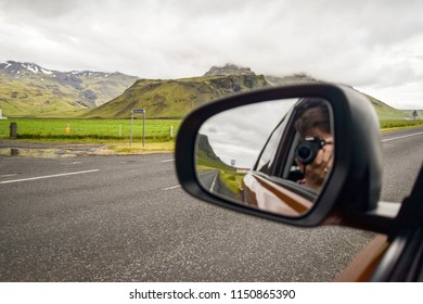 Man taking photo in rearview mirror of the view behind him.  Road trip concept.