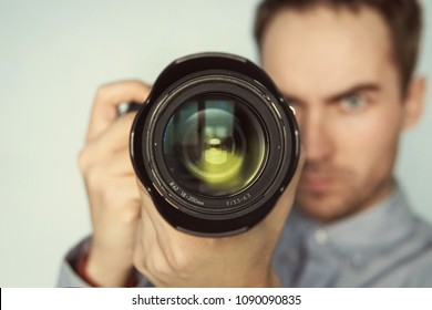 Man taking photo of you with mirrorless camera. young beautiful photographer with telephoto lens in hand on blue background. close-up camera lens