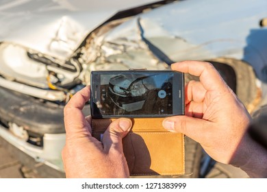 A man taking a photograph of a damaged car with his mobile phone