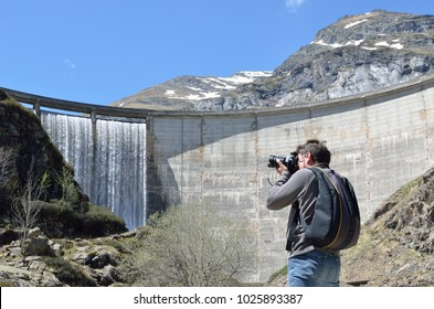 A man is taking a photograph of the Gloriettes dam on the Gave d'Estaube river in the Haute Pyrenees.