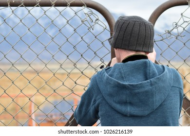 Man taking photograph of pond through fence.