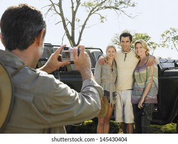 Man taking photograph of three friends against jeep