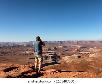 Man taking photos of the scenic Grand Canyon during a summer day