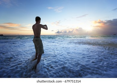 man taking photos of sunset on tropical beach by smartphone