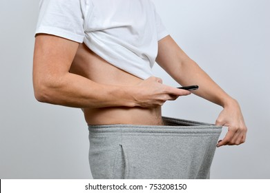 Man taking a picture of his penis with a smart-phone. A so-called dick pic