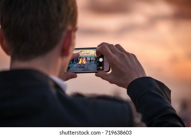 Man is taking picture of sunset with smart phone. Romantic bonfire night at seaside. People gathering together to celebrate Night of ancient lights. Large burning campfire with soft glowing flame.