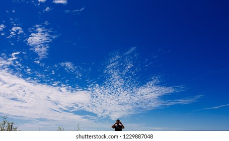 A man taking pictures of blue sky