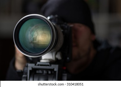 Man taking pictures of cheaters with a large telephoto lens