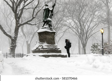 A man is taking pictures of the sculpture of Christopher Columbus in Central Park during a heavy snowfall.