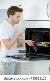 Man taking pie from oven, blowing fingers