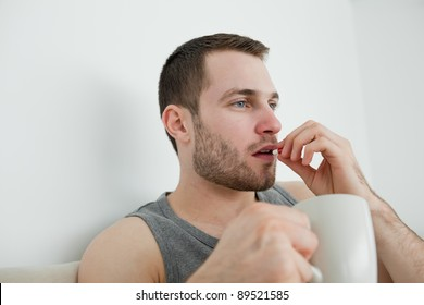 Man taking a pill in his bedroom