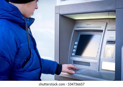 Man taking pin code on ATM