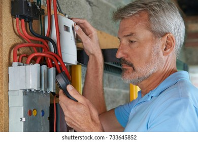 Man Taking Reading From Electricity Meter
