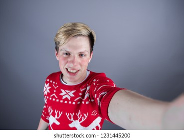 Man taking selfie with Camera while wearing a christmas sweater