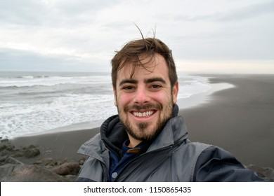 Man taking selfie in front of black sand lava beach in Iceland