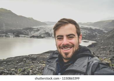 Man taking selfie in front of Solheimajokull Glacier in Iceland