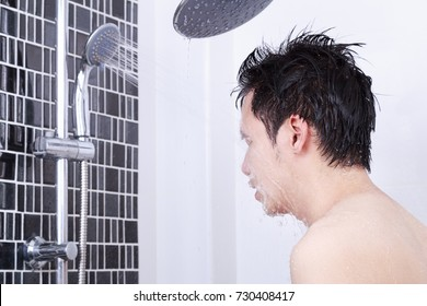man are taking a shower and washing face in the bathroom