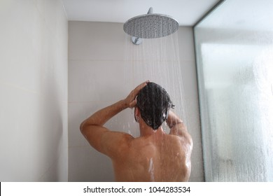Man taking a shower washing hair under water falling from rain showerhead. Showering person at home lifestyle. Young adult body care morning routine.