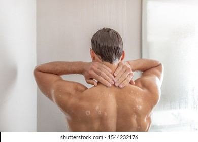 Man taking a shower washing hair under in luxury walk-in hot tub bath. Showering young person touching back of neck at home. Body care male beauty morning routine. Condo or hotel lifestyle.