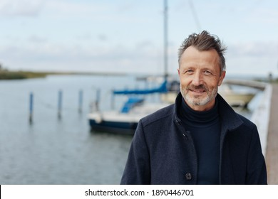 Man taking a stroll on a waterfront promenade in a warm overcoat on a cold autumn day in a close up portrait