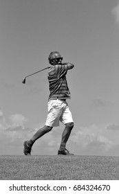 man taking a swing on gold course, black and white