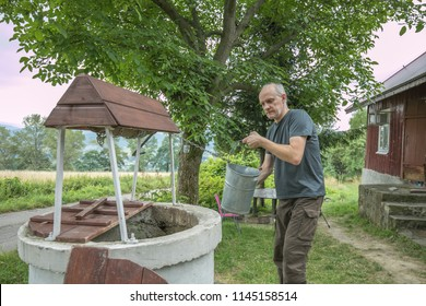 A man is taking the water from old, stone, water well  with a windlass and crank in the polish village. In the background view of the Cergowa Hill in the Low Beskids, Beskid Niski, Poland