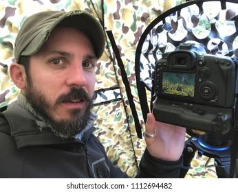 man taking wildlife photos from hide