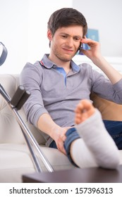 Man talking by phone with broken leg, having sad face