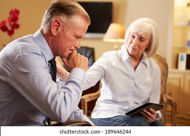 Man Talking To Female Counsellor Using Digital Tablet