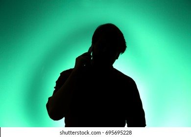 Man talking on cell phone in silhouette on green background