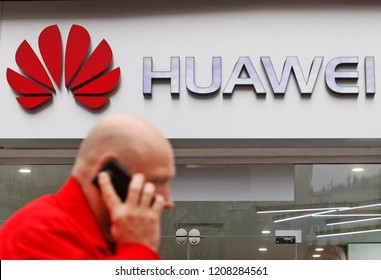 A man talking on the mobile phone as he walks next of Huawei brand store in Kiev, Ukraine, on 20 October 2018