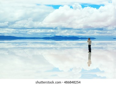 Man talking on the mobile phone in the middle of Salar de Uyuni, Bolivia